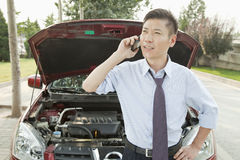 Worried Businessman Calling for Roadside Assistance Royalty Free Stock Photography