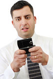 Worried Businessman On Cellphone. A young handsome businessman looking worried while texting on his cellphone over white Stock Photo