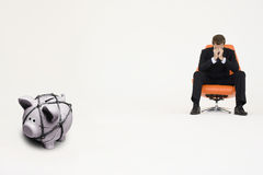 Worried businessman on chair and piggybank tied with rope representing financial difficulties Royalty Free Stock Photography