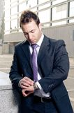 Worried businessman checking time Stock Image