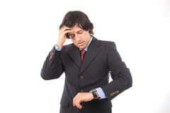 Worried businessman consulting his watch. Isolated on white background royalty free stock images