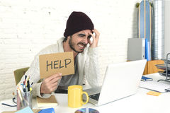 Worried businessman in cool hipster beanie look holding help sign working in stress at home office Stock Image