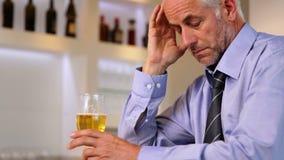 Worried businessman drinking a beer after work