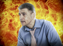 Worried businessman with fire in background Stock Photos