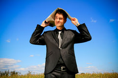 Worried businessman with folder above his head. Elegant business person holding a folder and cellphone Stock Images
