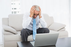 Worried businessman with head in hands in front of laptop at home Stock Images
