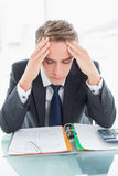 Worried businessman with head in hands at office desk Royalty Free Stock Image