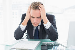 Worried businessman with head in hands at office desk Stock Photo
