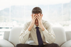 Worried businessman with head in hands sitting on couch Royalty Free Stock Photography