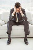 Worried businessman with head in hands sitting on couch Stock Photography