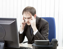 Worried businessman with a headache. Sitting at his desk, rubbing his temples with his fingertips and staring at his desktop computer monitor in despair Royalty Free Stock Photos