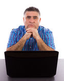 Worried businessman in his office. Portrait of a worried businessman in front of his laptop in the office Stock Photo