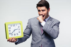 Worried businessman holding clock Royalty Free Stock Photo
