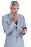 Worried businessman holding his cellphone Stock Image