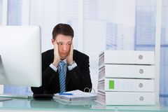 Worried businessman looking at binders on desk Royalty Free Stock Images