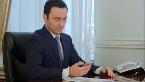Worried businessman looking on smartphone and reading bad news royalty free stock images