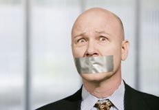 Worried businessman muzzled with duct tape Royalty Free Stock Image