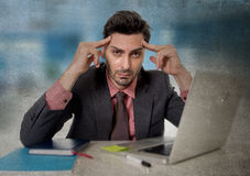 Worried businessman at office suffering headache working on computer desperate in work stress Royalty Free Stock Images