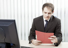 Worried businessman reading a document at his desk Stock Images