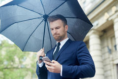 Messaging under umbrella. Worried businessman reading sms under umbrella outdoors royalty free stock images