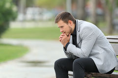 Worried businessman sitting on a bench. Side view portrait of a worried businessman sitting on a bench in a park Royalty Free Stock Photos