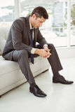 Worried businessman sitting on couch Stock Image