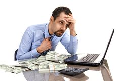 Worried businessman sitting at office desk being overloaded with work and accounting money Royalty Free Stock Images