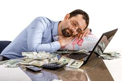 Worried businessman sleeping at office desk being overloaded with work and accounting money Stock Image