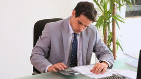 Worried businessman using a calculator. In his office stock footage