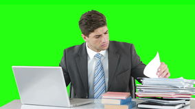 Worried businessman using laptop at desk. Against green background stock footage