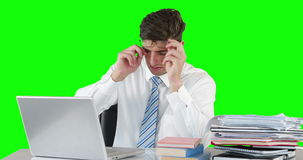 Worried businessman using laptop at desk. Against green background stock video