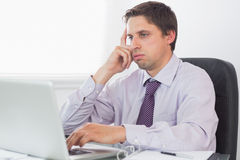 Worried businessman using laptop in office Royalty Free Stock Photography