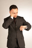 Worried businessman with watch Royalty Free Stock Photos
