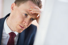 Worried businessman working at his desk Stock Image