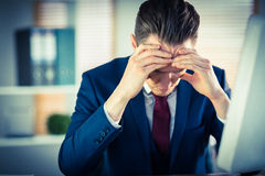 Worried businessman working at his desk Stock Photography