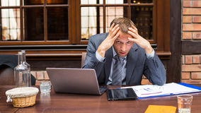 Worried businessman working in restaurant. Royalty Free Stock Photo
