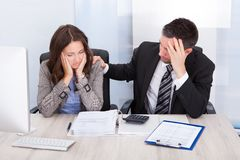 Worried businesspeople calculating finance Stock Photography