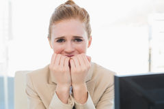 Worried businesswoman bitting nails at office Royalty Free Stock Image