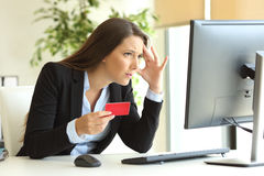 Worried businesswoman buying with credit card Royalty Free Stock Photography