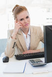 Worried businesswoman with computer at desk Stock Photography