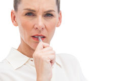 Worried businesswoman with pen on mouth. Looking at the camera Stock Photos