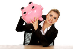 Worried businesswoman with a piggybank behind the desk Royalty Free Stock Photos