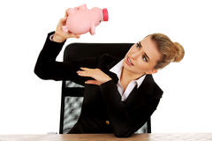 Worried businesswoman with a piggybank behind the desk Royalty Free Stock Image