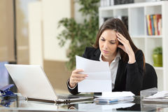 Worried businesswoman reading a notification. Sitting in a desktop at office Stock Image