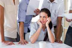 Worried businesswoman surrounded by colleagues Stock Images