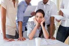 Worried businesswoman surrounded by colleagues Royalty Free Stock Photos