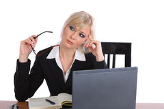 Worried businesswoman thinking. Attractive blond businesswoman with the worried expression on her face holding her eyeglasses and thinking Stock Image