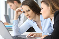 Worried businesswomen working on line. Two worried businesswomen working on line with a laptop at office Stock Images
