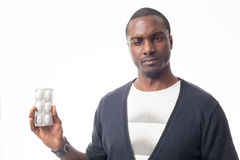 Worried cassual dressed black man with pack of pills. Isolated on white Royalty Free Stock Photo