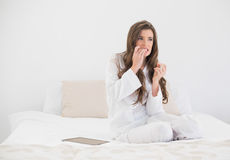 Worried casual brown haired woman in white pajamas sitting on her bed Stock Images